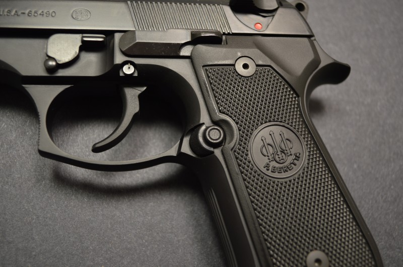 Checkered grip panels and button magazine release. The lever just forward and above the trigger is rotated clockwise to remove the slide assembly.